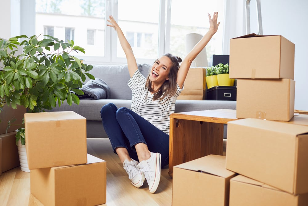 Student celebrating moving into new accommodation whilst surrounded by boxes